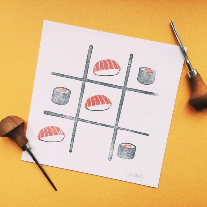 Linoleografia con sushi posizionati come pedine nel gioco del tris, sfondo giallo e sgorbie laterali